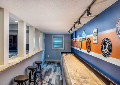 Basement Shuffleboard Room with Bar Stools and Man Cave Signs