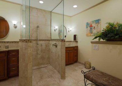 Twin Vanity Sinks and Mirrors with Walk-in Shower in between and Bench