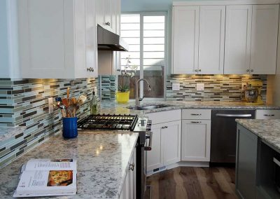 Hi Tech Kitchen Remodel with White Cabinets Marble Counters and Colorful Slim Tile Backsplash