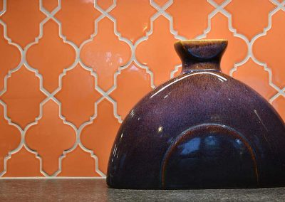 Orange Arabesque Tile Kitchen Backsplash with Purple Ceramic Vase