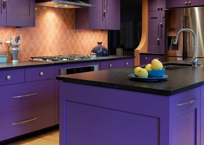 Island Countertop with Purple Features and Orange Tile Backsplash behind Stove