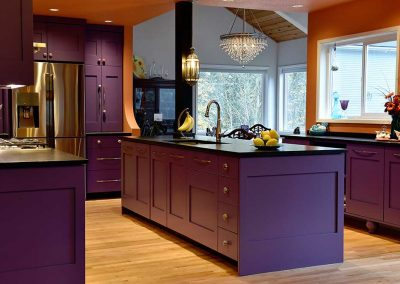 Open Concept Kitchen with funky Purple and Orange Design and Bohemian Fixtures
