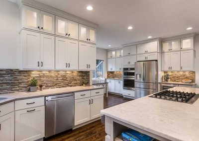 Contemporary Kitchen Design with White Cabinets Recessed Lighting and Assorted Stone Tile Backsplash