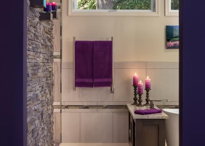 Master Bath with Arch Doorway Stone Wall and Purple Decor