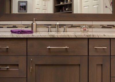 Master Bathroom Vanity with Brown Matte Wood Cabinets and Tile Backsplash