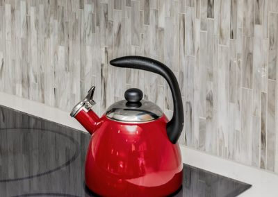 Red Tea Kettle on Smooth Top Stove with Tile Backsplash